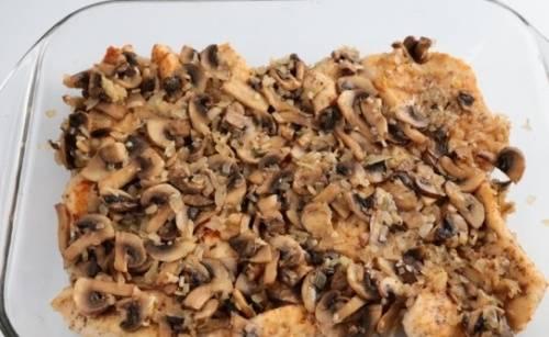 Сверху мяса равномерно распределяем грибы с луком.
