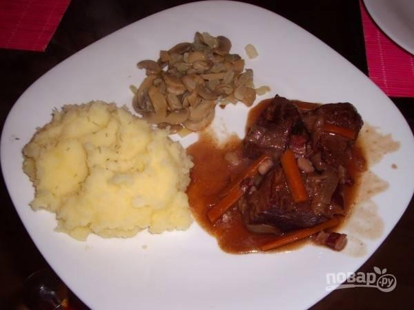 7.Выпекаю мясо четыре часа, после этого подаю его с пюре из картофеля и жаренными грибами.