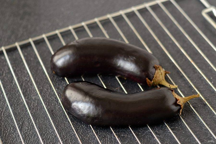 Разогрейте духовку до 250 градусов. Баклажаны промойте в холодной воде, аккуратно отожмите. Выложите их разрезом вниз на решетку. Запекайте 10 минут.