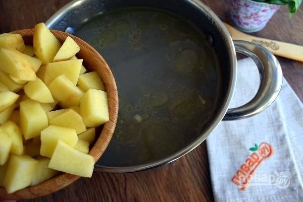 Куриный бульон доведите до кипения. Картофель  нарежьте мелкими кубиками, положите в бульон, накройте крышкой и варите до мягкости на медленном огне.