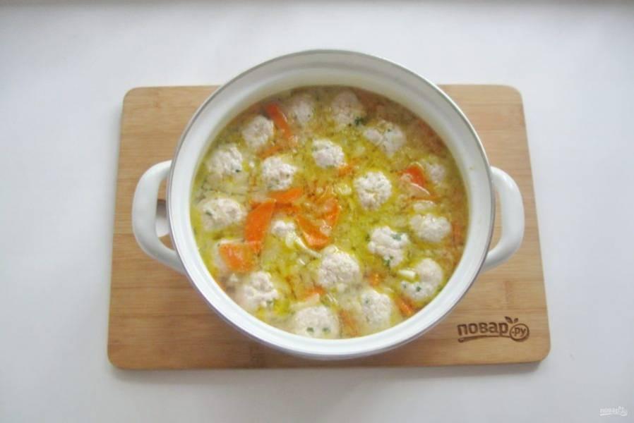 Выложите фрикадельки в кипящий суп. Посолите по вкусу.