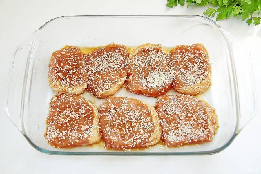 7. Достаньте маринованные отбивные и выложите их в один слой в смазанную маслом форму для запекания. Сверху посыпьте равномерно кунжутом. Отправьте в духовку и готовьте при 200*с около 30 минут.