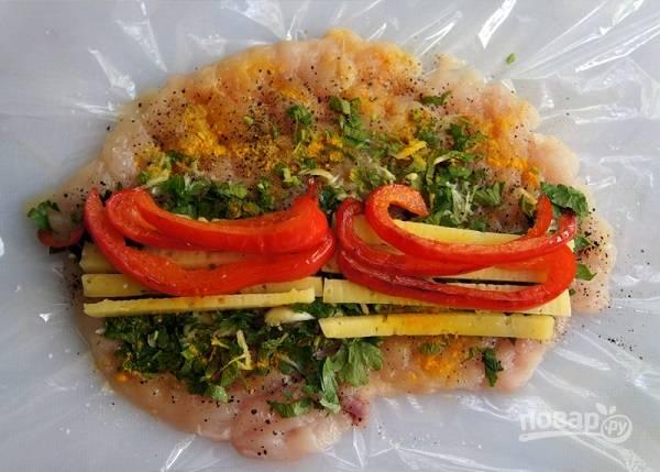 3. Филе посолите, добавьте черный перец и паприку по вкусу. Распределите зелень с чесноком. Выложите перец и сыр.
