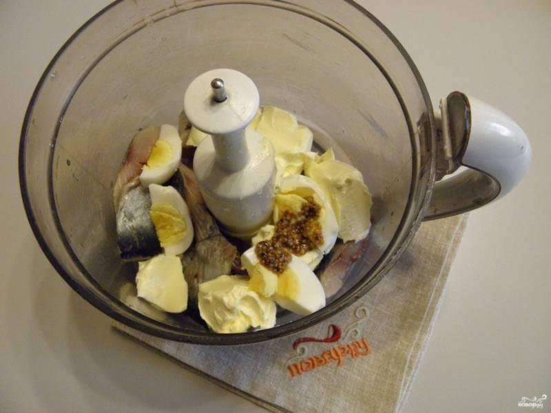 В чашу измельчителя положите кусочки сельди, вареное яйцо, сливочное масло, горчицу, выдавите лимонный сок.