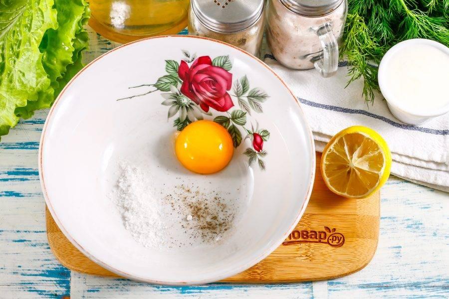 Аккуратно разбейте куриное яйцо и удалите белок - он в рецепте не потребуется. Желток выложите в глубокую емкость, всыпьте соль и молотый черный перец.