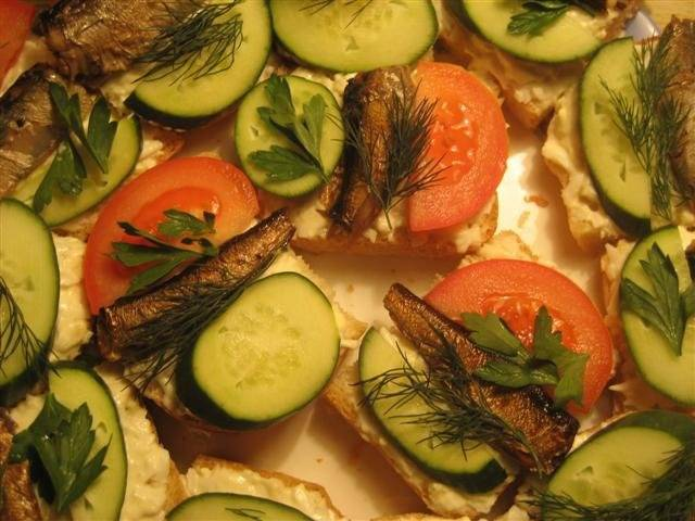 Сверху кладем шпроты, огурцы и помидоры (порезанные кружочками). Украшаем зеленью, приятного аппетита!