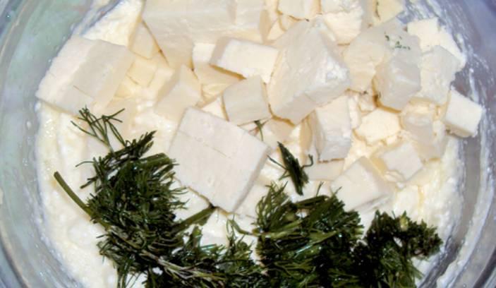 Смешиваем в глубокой тарелке измельченную зелень с творогом и адыгейским сыром. Вбиваем два яйца, перемешиваем до однородности.