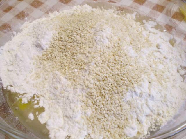 3. Разделите сырое яйцо на желток и белок. Желток отложите, он понадобится для смазывания бубликов перед выпеканием. Белок вводим с растительным маслом в полученную смесь. Добавляем пшеничную муку, кунжут, ванилин. Количество кунжута - на ваше усмотрение.