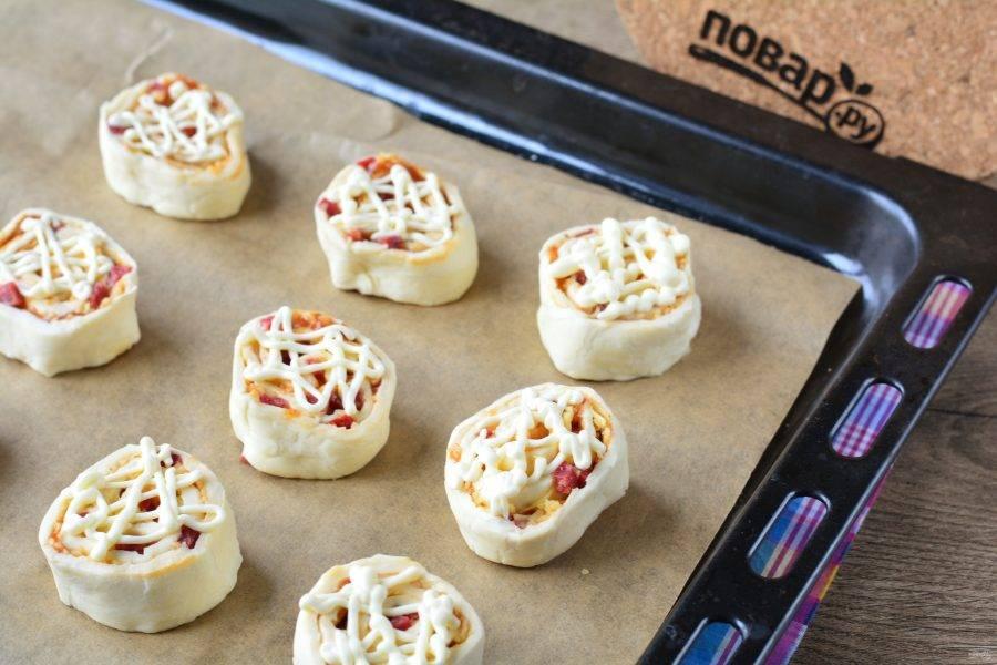 Выложите мини-пиццы на противень и слегка полейте майонезом.