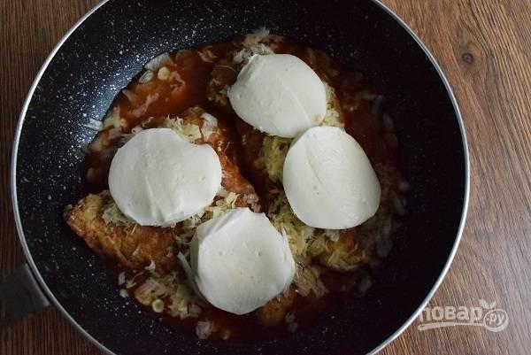 Духовку разогрейте до 180 °C. Опустите куриные грудки в томатный соус, посыпьте сверху тертым пармезаном, положите ломтики моцареллы.