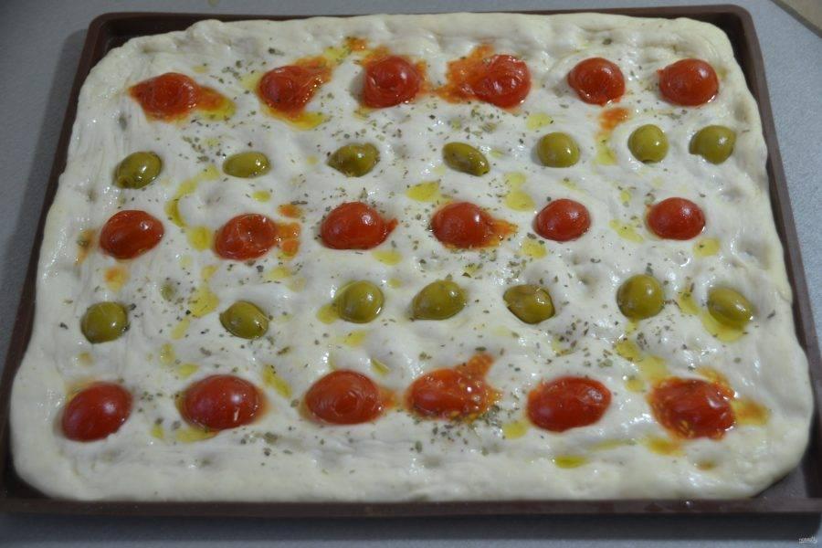 Выложите произвольно начинку, слегка вдавливая её в тесто, посыпьте сухим орегано.