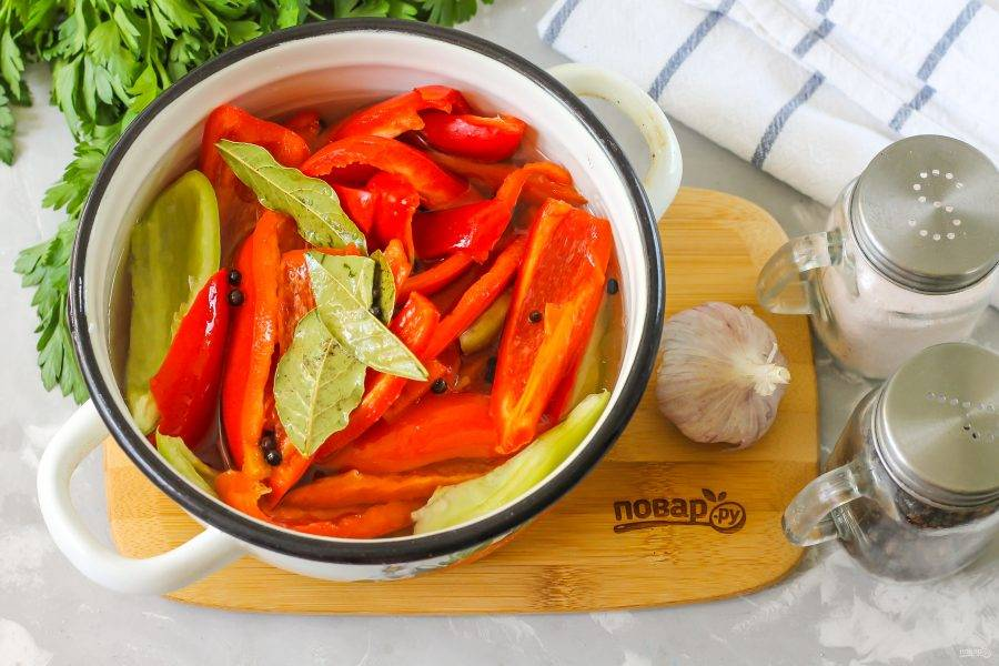 Выложите нарезку болгарского перца в другую емкость. Очистите от шелухи чесночный зубчик и промойте его, нарежьте в емкость, залейте все кипящим маринадом. Оставьте на 30-40 минут до полного остывания, время от времени перемешивая содержимое емкости для равномерного приготовления.