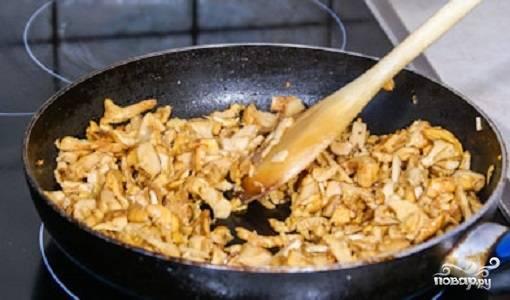 Возьмите еще одну сковороду. Растопите на ней сливочное масло. Затем добавьте грибы. Лисички  содержат много влаги, потому жарьте их до тех пор, пока вся вода не испарится. После того, как лисички пожарены, посолите их, добавьте муку. Тщательно перемешайте грибы. Важно равномерно распределить муку. Подержите лисички на огне еще несколько минут.