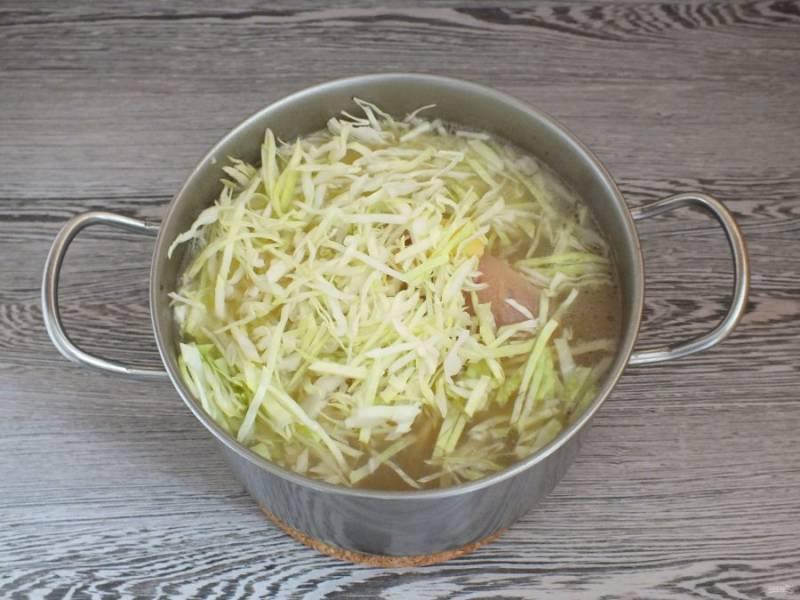 В кастрюлю с рулькой опустите картофель нарезанный соломкой и капусту. Проварите все вместе в течение 30 минут.