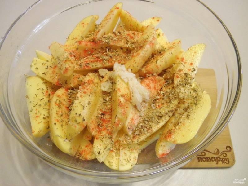 В картофель добавьте пропущенные через пресс чеснок, орегано, паприку, соль, перец. Тщательно руками перемешайте картофель.