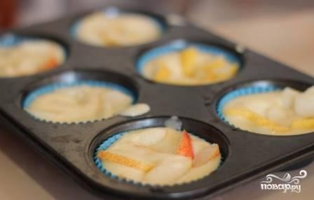 Выкладываем тесто в формочки на 2/3 высоты и сверху выкладываем ломтики груш, слегка вдавливая их в тесто.