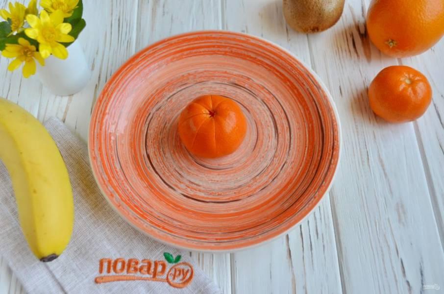Прощупайте пальцами мандарин и постарайтесь определить, как идут дольки. Острым ножом порежьте на 8 частей до половины кожуру мандаринки. Сами же дольки постарайтесь не задеть.