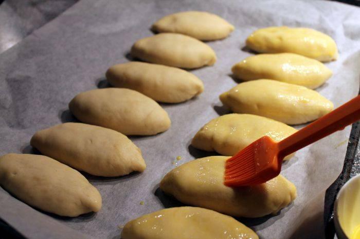На противень выкладываем пергамент. Выкладываем пирожки, даем расстояться 30-40 минут. Затем смазываем взбитым яйцом и отправляем запекаться в предварительно разогретую до 190-200 градусов духовку на 20-25 минут.
