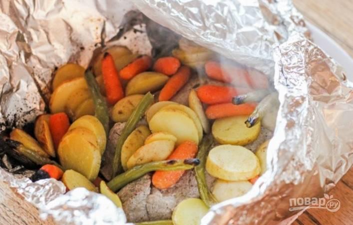 Картофель промойте хорошенько и нарежьте кружочками или тонкими дольками, смешайте все овощи с маслом, тмином и чесночной солью, выложите к мясу.