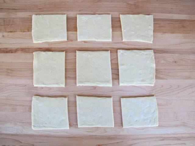 2. Готовое размороженное тесто выложите на присыпанную мукой рабочую поверхность. Разрежьте на равные квадраты, сторона которых равна (плюс-минус) 8 см.