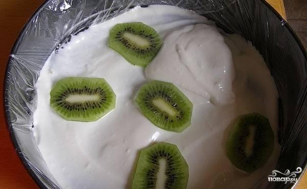 На ананасы - творожную смесь, дольки киви, затем опять творожную смесь и дольки персиков, покрываем все оставшейся творожной смесью. Отправляем торт в холодильник для застывания.