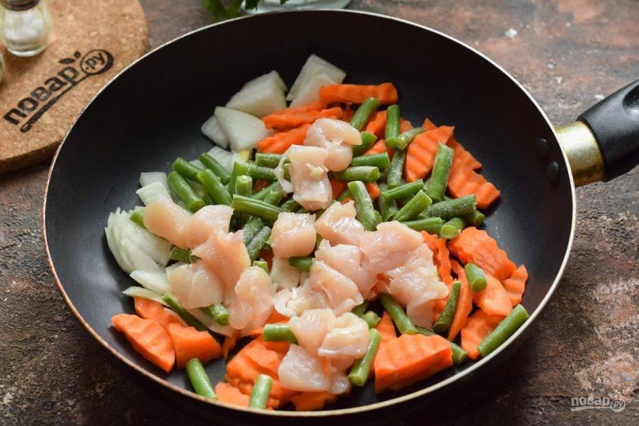 Куриное филе нарежьте небольшими кубиками и добавьте к овощам.