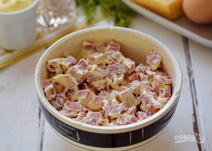 Перекладываем колбасу в салатницу, сверху покрываем слоем майонеза.