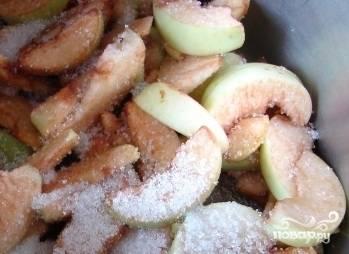 Переложить яблоки в кастрюлю, засыпать сахаром и перемешать.