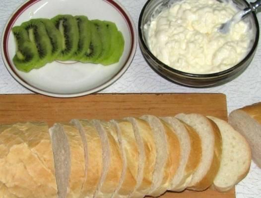 Итак, для начала нарезаем багет на ломтики шириной около 1,5 см, киви очищаем от кожуры и нарезаем его кружочками. Теперь приготовим сырную массу, для этого нам необходимо размять сырок вилкой, если он мягкий, или натереть его на крупной терке. Затем добавляем к сырку майонез и пропущенный через пресс чеснок, хорошенько все перемешиваем до однородного состояния.