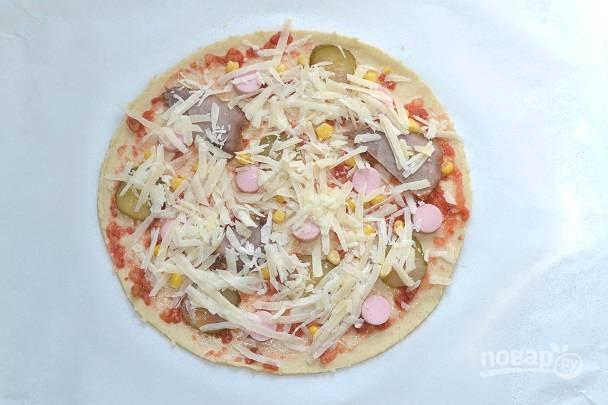 Смажьте тесто соусом, распределите начинку и присыпьте сверху сыр. Отправьте в разогретую до 200 градусов духовку.