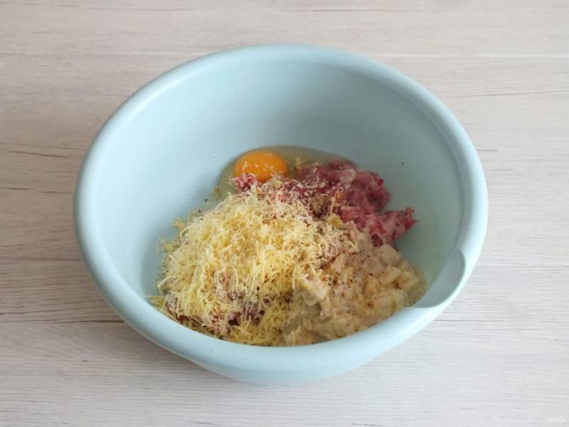 Добавьте яйцо, тертый на мелкой терке сыр. Посолите, добавьте перец по вкусу.