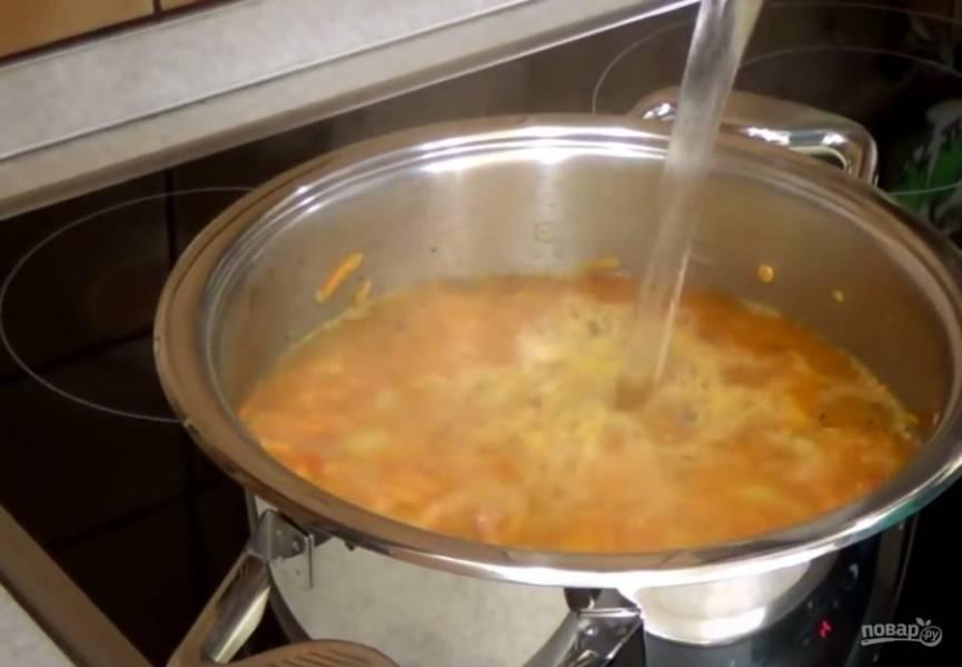 3.  Добавьте очищенный от кожуры и нарезанный кубиками помидор и промытую чечевицу. Залейте овощи кипятком и доведите до кипения, после чего уменьшите огонь и варите под закрытой крышкой 20-25 минут.