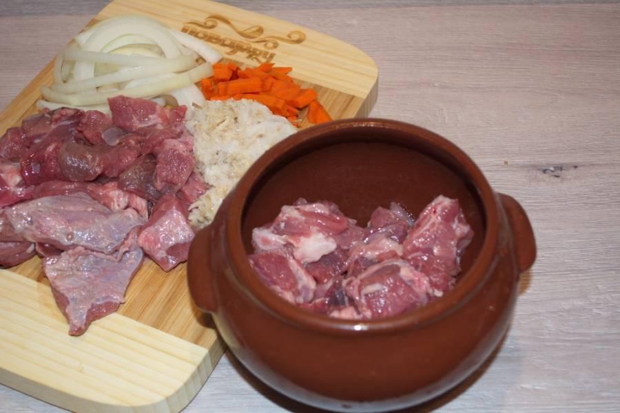 Возьмите глубокий горшочек. Смажьте его внутри маслом. На дно горшочка уложите смесь лука и моркови. Сверху положите нарезанное мясо.