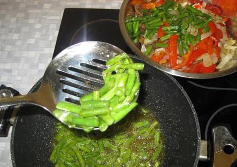 В той же сковородку обжариваем стручковую фасоль. Обжариваем ее быстро - около 4 минут. Затем перекладываем ее ко всем другим компонентам.