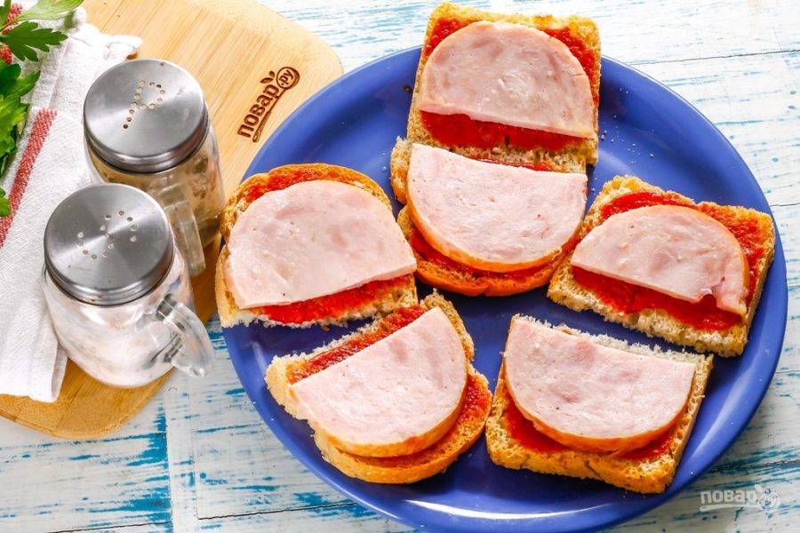 Ветчину нарежьте кружочками, а кружочки - разрежьте пополам и выложите на слой кетчупа. Вместо ветчины можно использовать копченое мясо, колбасу: копченую или вареную.