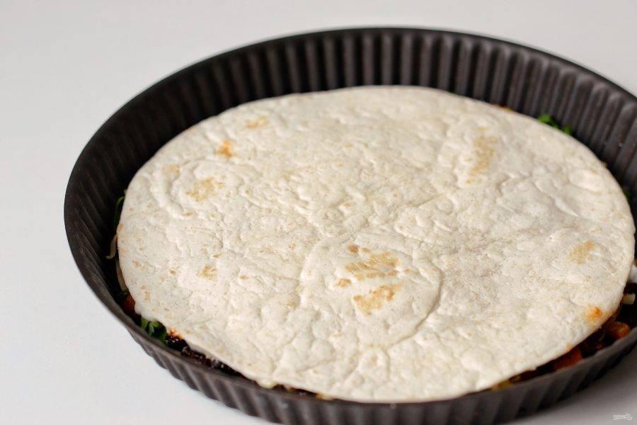 Смажьте вторую лепешка майонезом, накройте нижнюю. Выпекайте тортилью в заранее разогретой до 180 градусов духовке 5-8 минут.