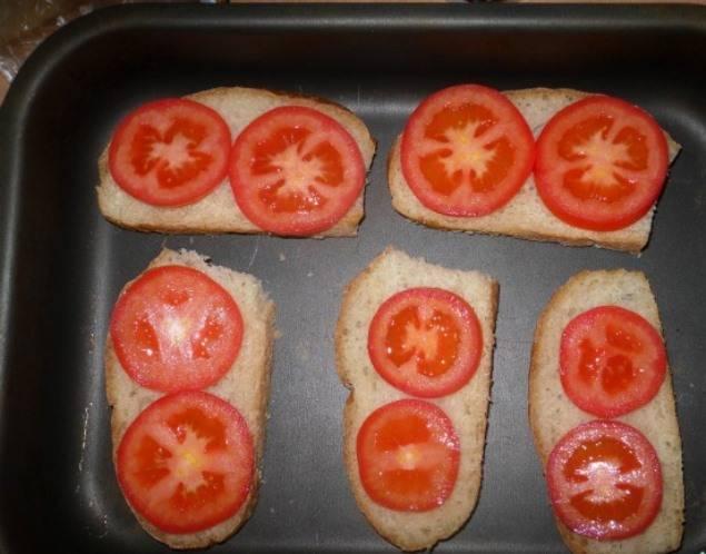 Порежьте батон и помидоры, кусочки помидоров уложите на ломтики батона.