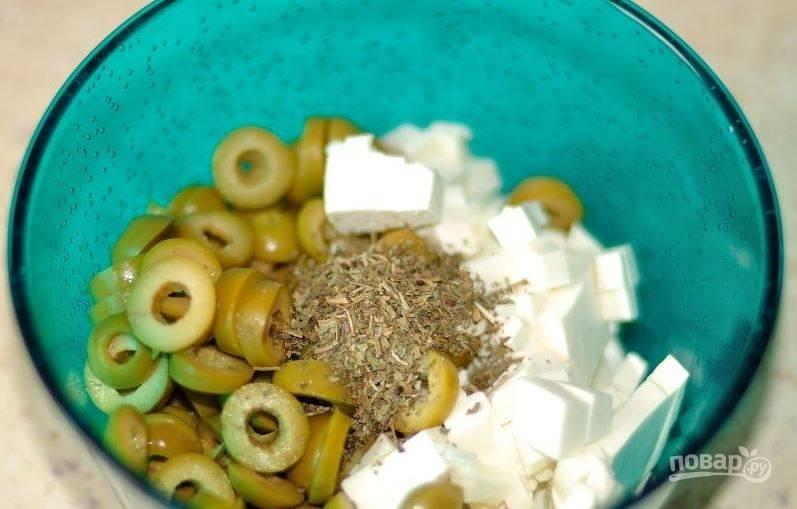 Откройте банку зеленых оливок без косточек, слейте с них лишнюю жидкость и нарежьте оливки кружочками. Затем порубите кубиками брынзу или фету. Выложите их в миску, добавьте сушеный базилик. Тщательно перемешайте. Это будет начинка для помидоров.