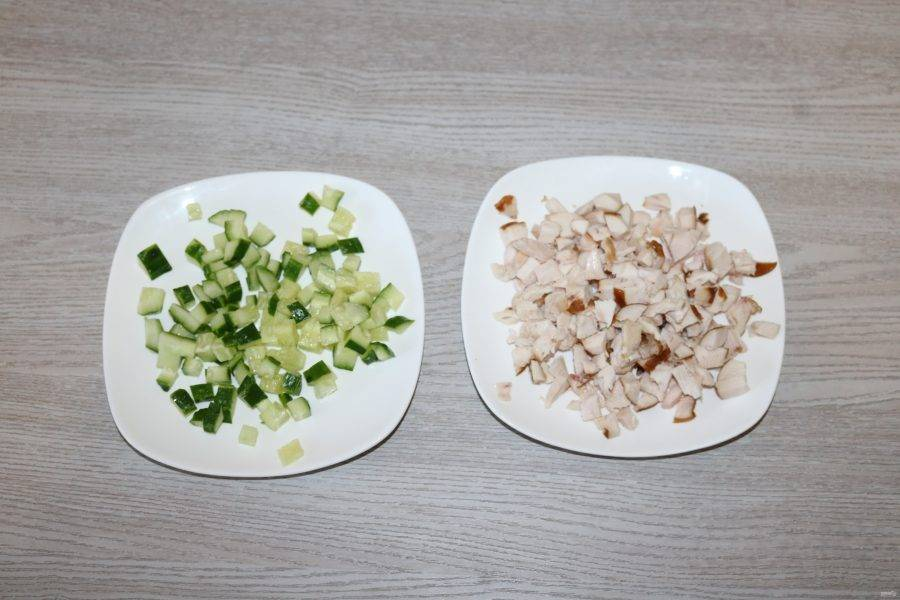 Огурец и куриную грудку нарежьте кубиками. Яйца куриные натрите на крупной тёрке. Сыр натрите на мелкой тёрке.