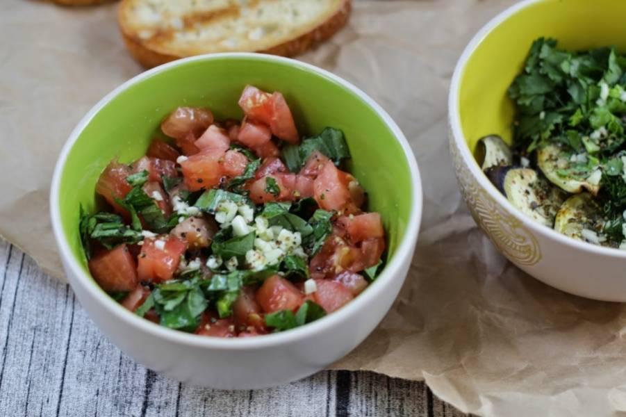 Помидоры режем кубиками, добавляем к ним базилик и тоже немного чеснока. Заправляем оливковым маслом.