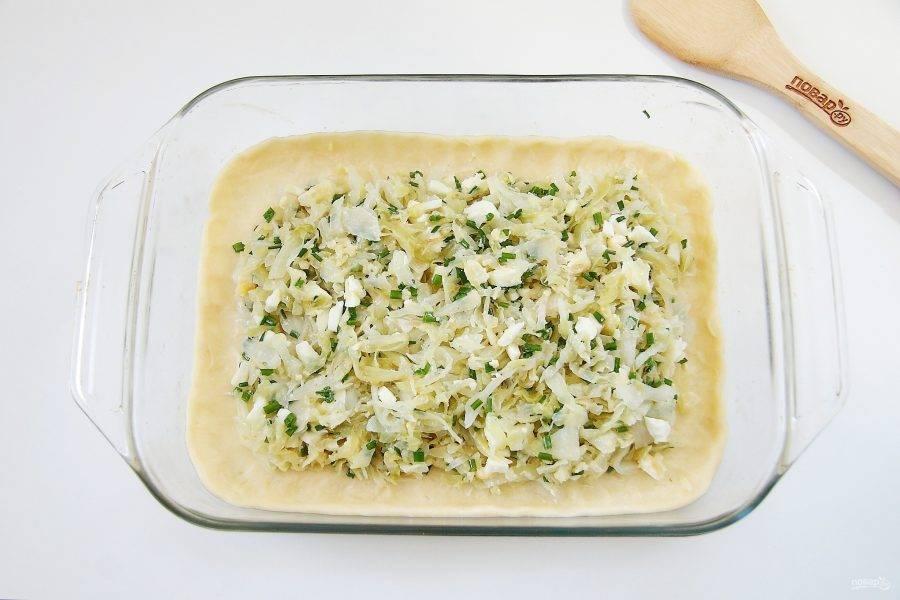 Большую часть раскатайте в виде прямоугольника и перенесите в смазанную маслом форму для выпечки. Сверху равномерно распределите начинку, отступив немного от краев.