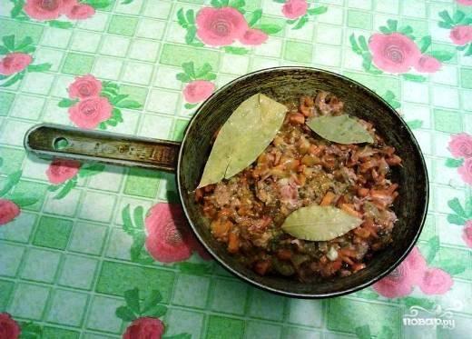 Овощи на сковороде уже немного остыли, добавим к ним тушенку, лавровый лист и можно еще черный молотый перец или другие приправы.