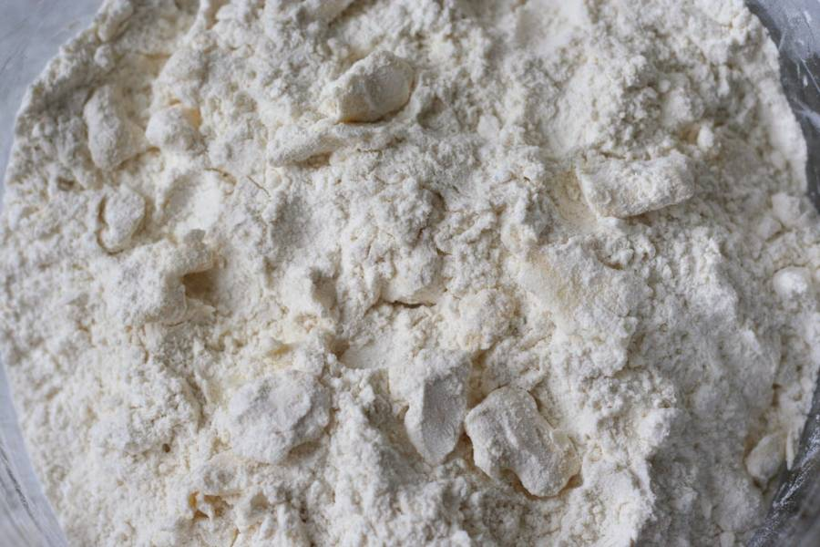 1. Просеем муку с сахаром и разрыхлителем. Вливаем молоко, замешиваем плотное тесто. В последнюю очередь добавим масло комнатной температуры. Замесим руками однородное тесто.