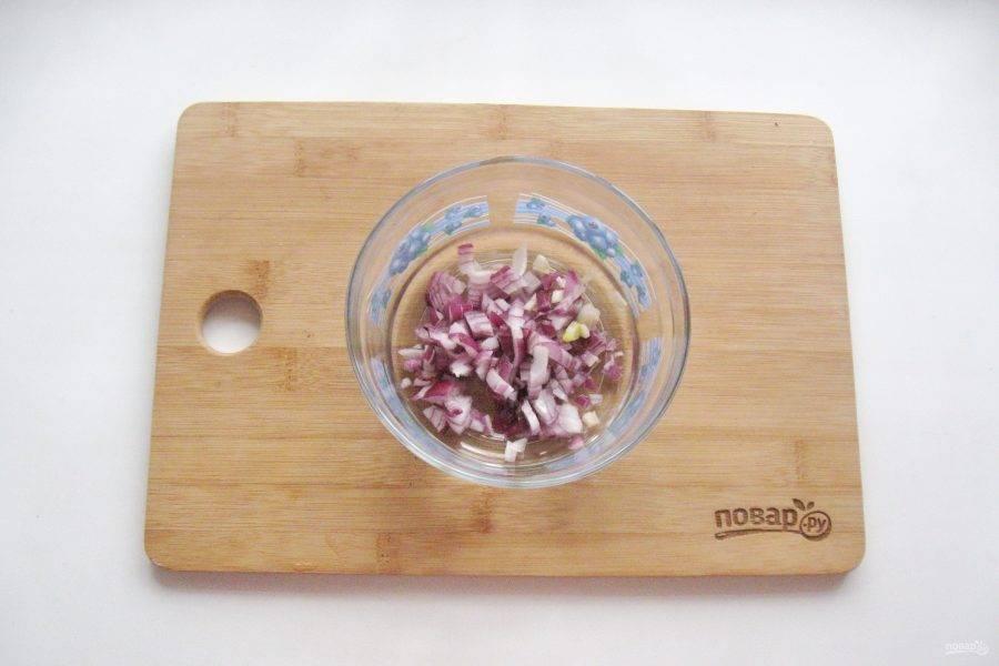 Фиолетовый лук мелко нарежьте и выложите в салатник.