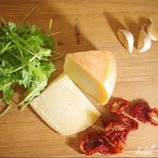 Подготовим ингредиенты. Измельченный чеснок обжарим слегка обжарим на оливковом масле вместе с вялеными помидорами (буквально 1-2 минуты, до приятного аромата), рукколу хорошенько промоем, пармезан натрем на терке.