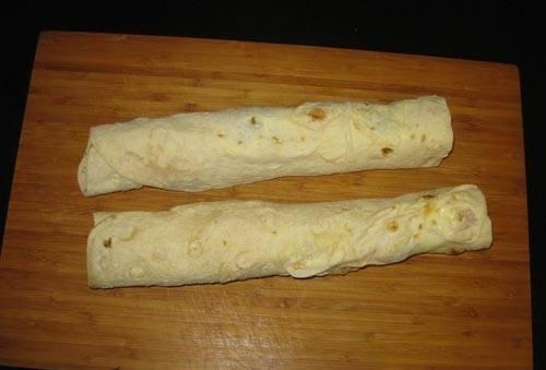 10. Если край прилегает не слишком плотно, еще раз промажьте его сыром. Разрежьте рулет из лаваша с ветчиной и сыром в домашних условиях на 2-3 части, заверните в пищевую пленку и уберите в холодильник.
