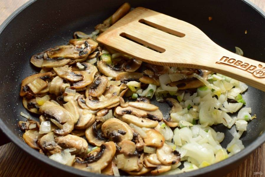 Грибы и лук (1 шт.) нарежьте тонкими ломтиками. На разогретом растительном масле (1 ст. л.) обжарьте грибы до румяной корочки, добавьте лук и готовьте до его мягкости. Посолите и поперчите по вкусу.