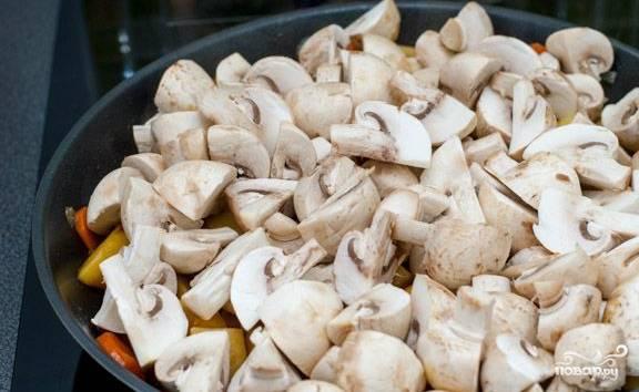 Накрываем сковороду крышкой, добавляем немного воды, тушим в течение 5-7 минут, иногда помешивая. В конце этого этапа добавляем соль и перец.  Проверяем готовность картошки. Если ломтики уже стали мягкими, пора выкладывать шампиньоны. Снова ждем 5 минут.
