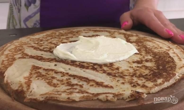 6. На каждый блин выложите ложку творожного крема, размажьте его тонким слоем. Сверните блин пополам, и еще раз напополам.