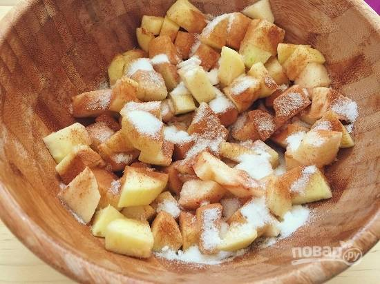 Выложим нарезанные яблоки в миску, добавим 2 столовые ложки белого сахара, корицу и муку. Перемешаем и пусть постоят минут 15.